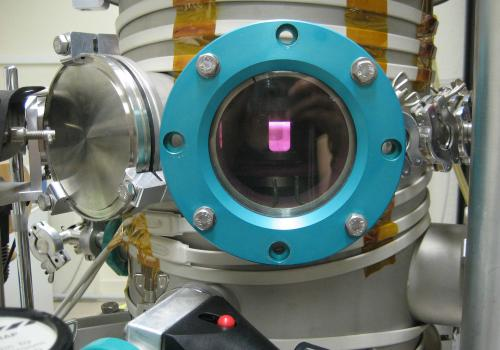 A window into Titan's atmosphere: Energized by microwaves, the gas mix inside the reaction chamber lights up like a pink neon sign. Thousands of complex organic molecules accumulated on the bottom of the chamber during this experiment.