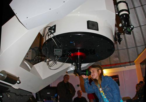A young visitor peers through the Schulman Telescope during a SkyNights public observing event.