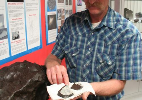 LPL curator Marvin Killgore holds the fragments of an object that exploded over the skies of Wisconsin several weeks ago, one of nearly three dozen meteorites he will exhibit this weekend at Foothills Mall.