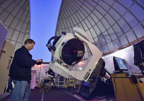 Adam Block adjusts the telescope to point to an object in the evening sky.