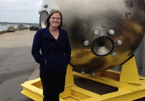 Bonnie Hurwitz next to the metal pod that serves as the main chamber for the Alvin submersible that scientists operate to collect samples from the deepest parts of the ocean not accessible to people. Photo taken at Woods Hole Oceanographic Institution.