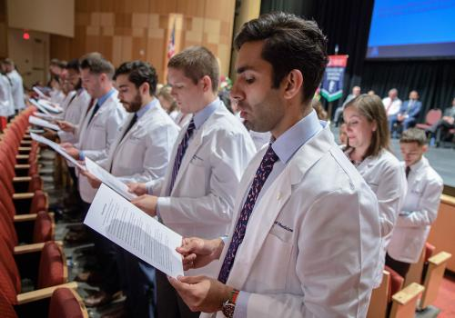 After receiving their white coats, medical students recited an oath acknowledging their dedication to patients.