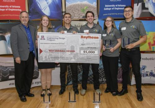 Raytheon's Victor Wagner, left, presents the top Design Day prize to a team of seniors who built a network of safety beacons for remote areas.