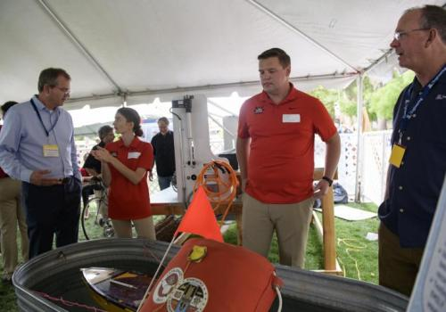 David Hahn, left, incoming dean of the College of Engineering, talks with a student about her work on the EMILY rescue robot, while a teammate and interim Dean Larry Head look on.