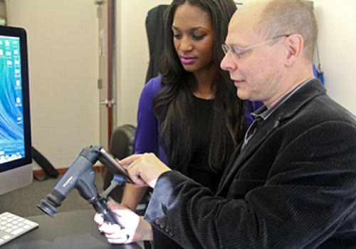 """Biomedical engineering student Jerri-Lynn Kincade and Wolfgang Fink select images of the eye's interior on a smartphone to be sent to a remote """"expert system"""" for subsequent analysis."""