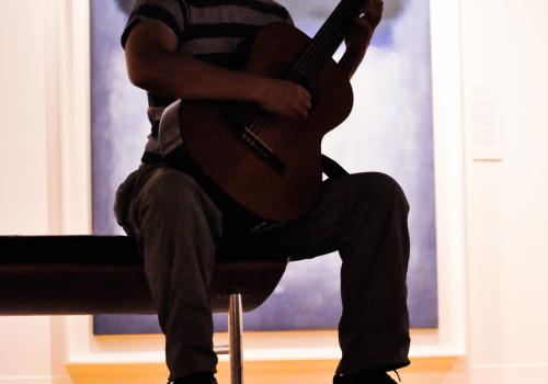 Chilean Master's student and Fulbright scholar Pablo Gonzalez cradles a guitar at one of the regular Friday morning performances at the UA Museum of Art.