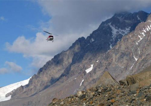 A helicopter lands in the Dry Valleys. Helicopters are used to transport personnel and cargo to field camps within a 100-mile radius of McMurdo Station.