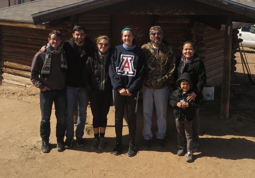 Karletta Chief  stands outside of the hoghaan with her son Ji'Hozho, Earl Tulley, and UA graduate students in the Indige-FEWSS program.