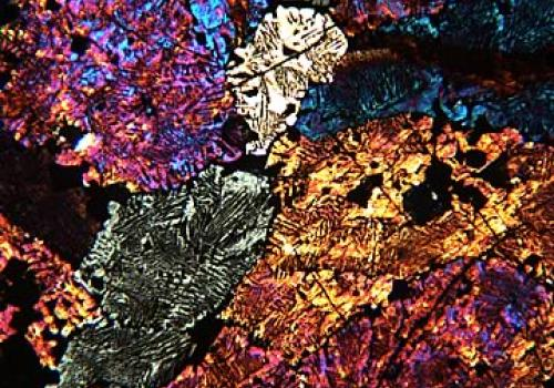 A metallurgical slag from ancient iron smelting in Madagascar. A thin slice was glued to a glass slide and polished to a thickness of only 0.03 mm. It is photographed here at a magnification of 200x in cross polarized transmitted light. All of the brightl