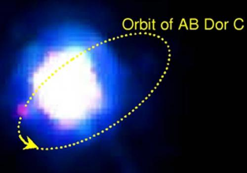 "An enhanced false color infrared image of AB Dor A and C. The faintcompanion ""AB Dor C"" -- seen as the pink dot at 8 O'clock -- is 120times fainter than its primary star. The tiny 0.156 arcsec separation between A and C issmaller than a dim"