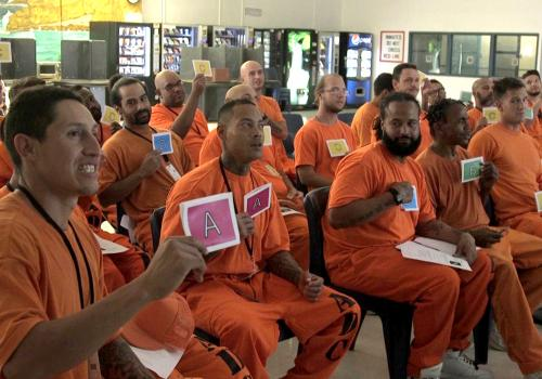 Incarcerated students vote on questions using colored cards.