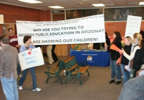 Protesters lined up with signs to meet Arizona House of Representatives Committee on Education.