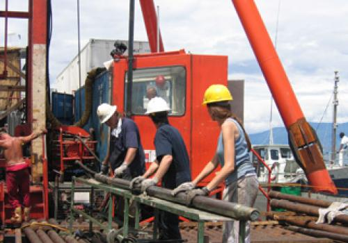 Members of the Lake Malawi Drilling Project science team handle the corer -- part of the equipment used to collect sediment cores from the bottom Lake Malawi. Note the sediment in the end of the metal tube. Photo credit: Courtesy of the Lake Malawi Drill