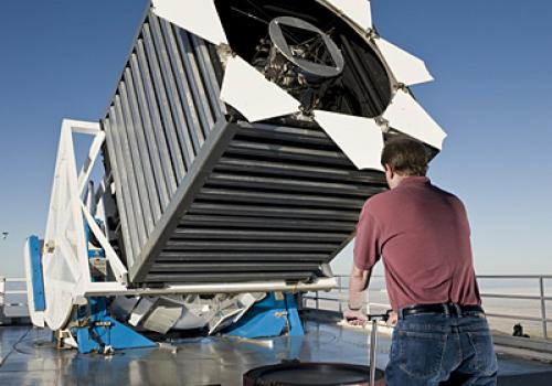 "Engineer Dan Long loads the first cartridge of the night into the Sloan Digital Sky Survey telescope. The cartridge holds ""plug-plates"" at the top, which then hold a thousand optical fibers shown in red and blue. The cartridges are locked into the base of"
