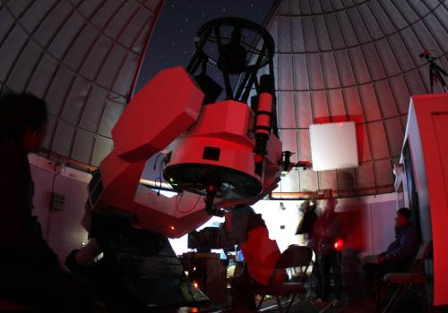 Bundled up against the chilly air on top of Mt. Lemmon, students use the Schulman Telescope for a night of observing planets, stars and galaxies.
