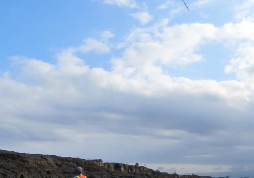 Stephen Scheidt flying a kite over the December 1974 flow in Hawaii.