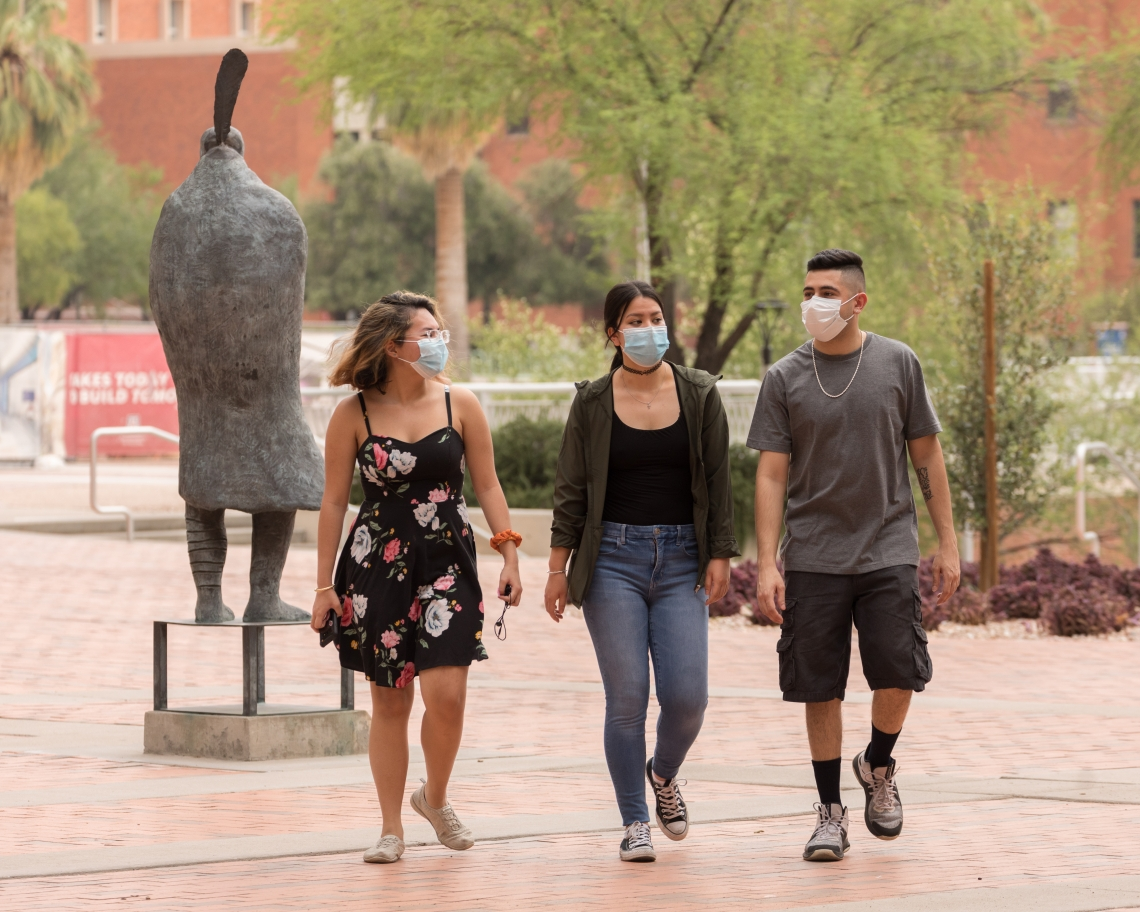 three students wearing face coverings walking on campus
