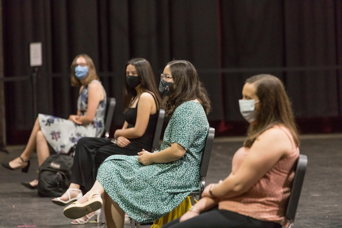 four female students wearing masks, seated spaced apart