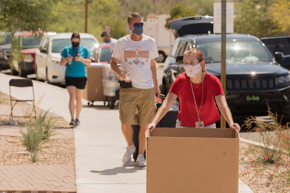 mask-wearing student with a large cardboard box moving into the dorm