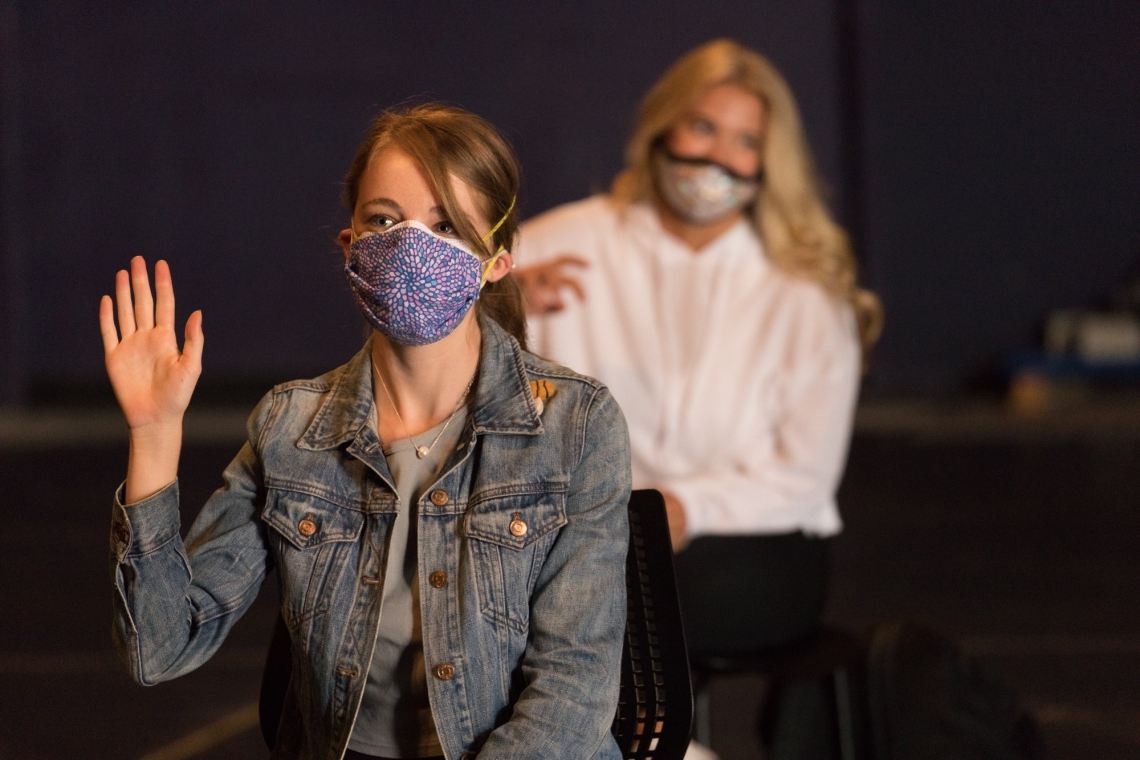 a female student wearing a mask raises her hand in the foreground and another masked female student sits in the background