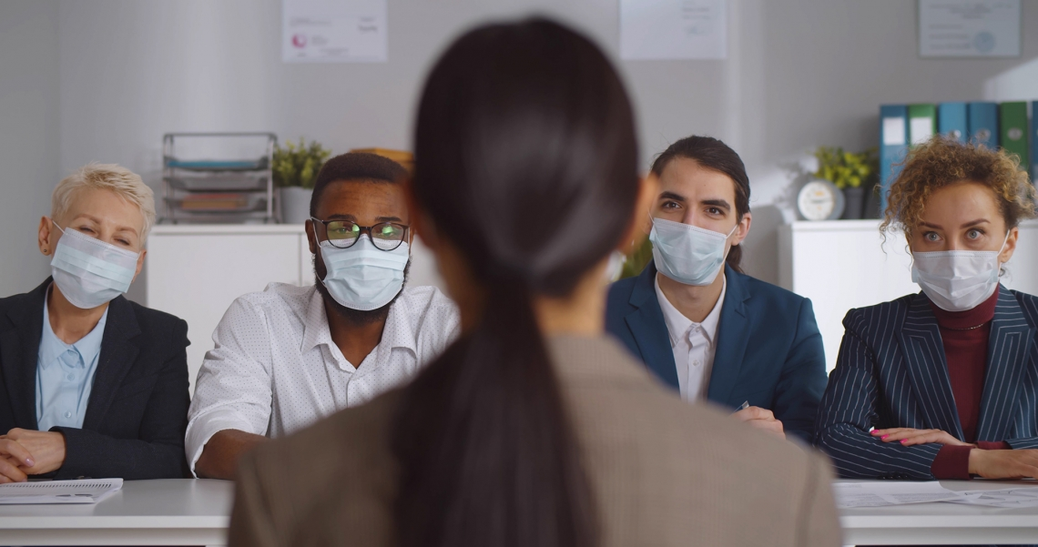 woman being interviewed by four people wearing masks