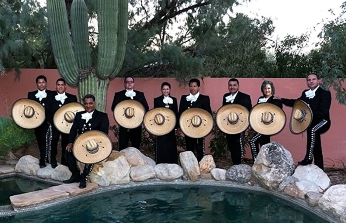 mariachi band posing near a pool
