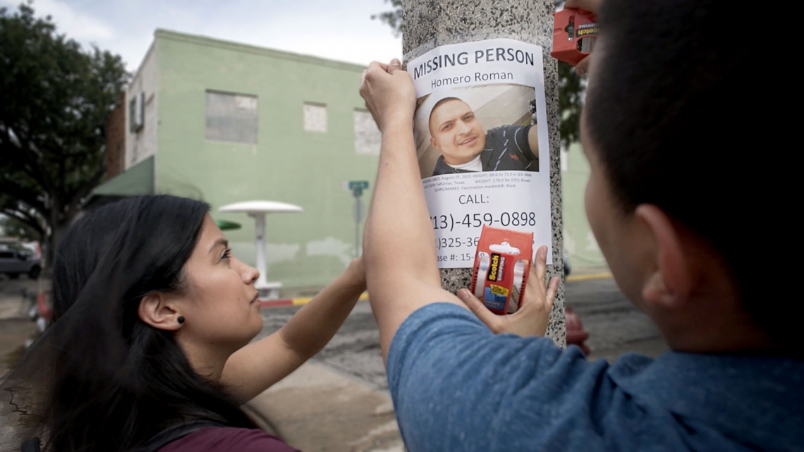a man and a woman hanging up a missing person flyer