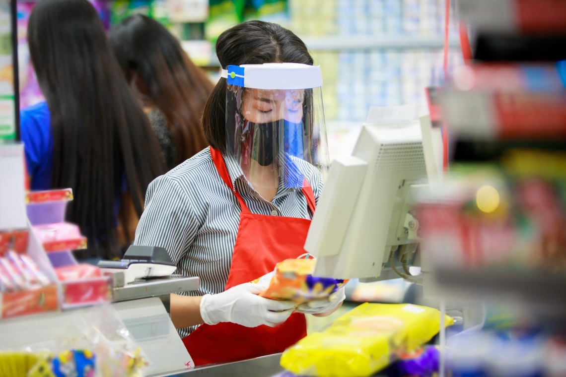 female cashier wearing mask and face shield ringing up groceries
