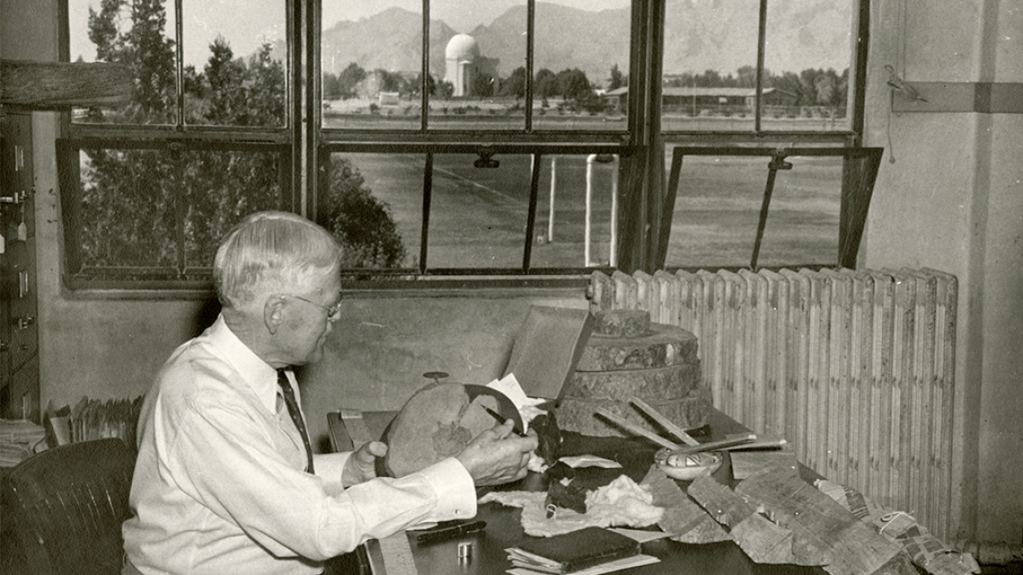 Andrew Ellicott Douglass at desk with pieces of wood
