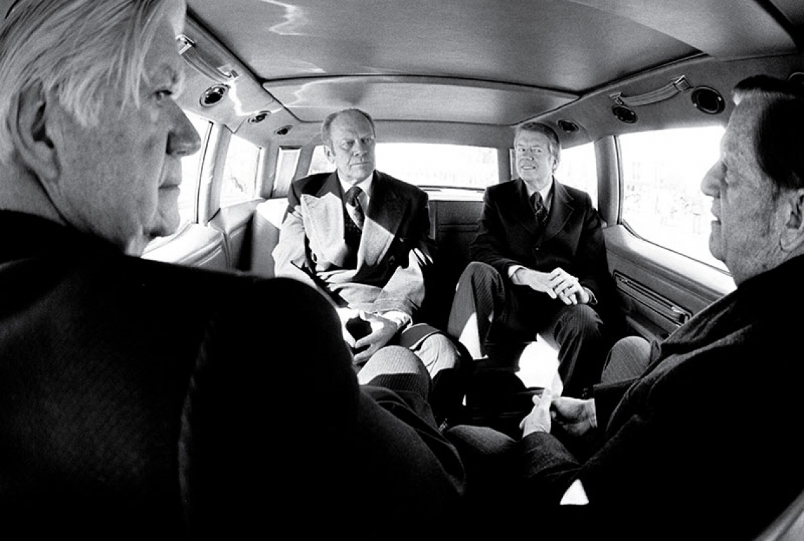 A black and white photograph of President Gerald Ford, President-Elect Jimmy Carter, Senator Howard Cannon and Speaker of the House Tip O'Neill on their way to Carter's inauguration