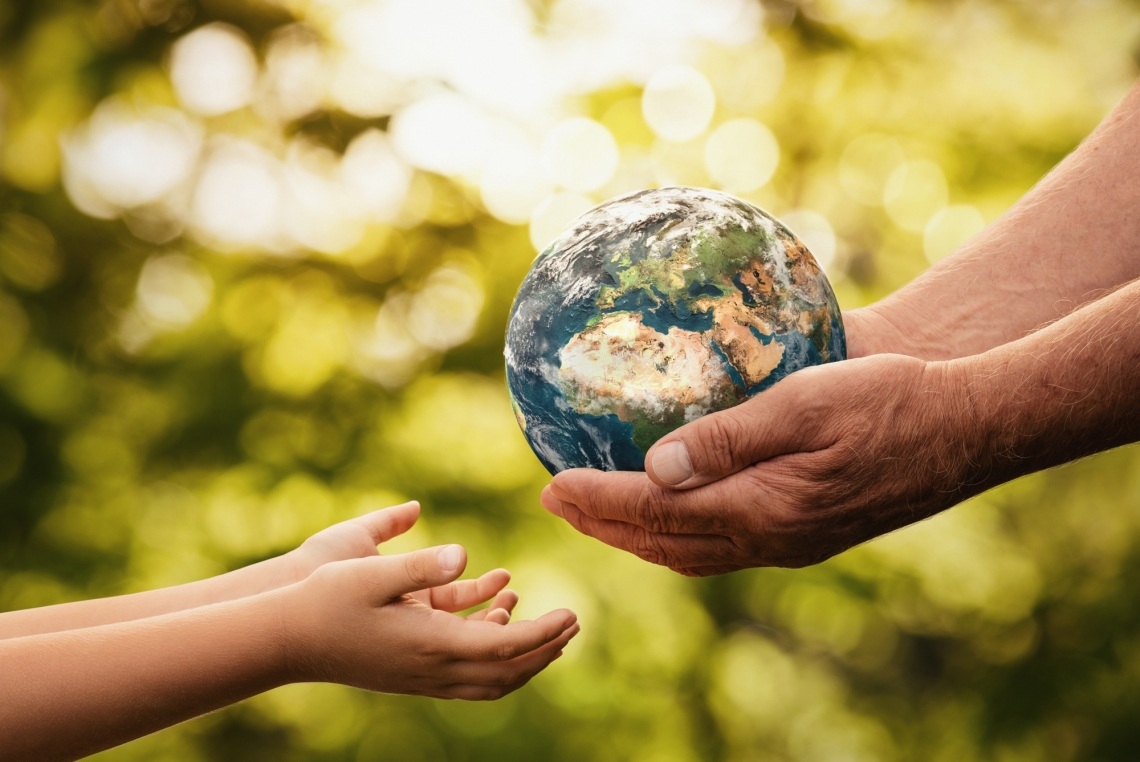 adult hands passing a small replica of Earth into a child's hands