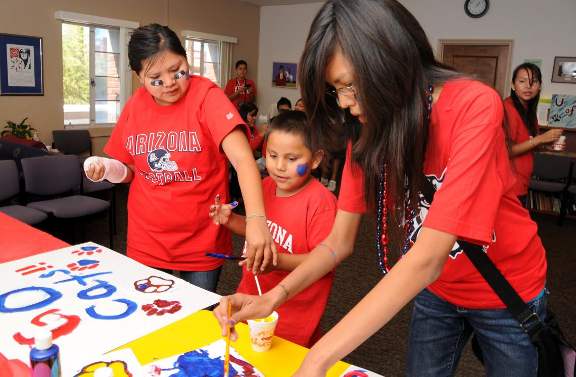 Ashley Scott, 16, , 6-year-old Denim Manygoats and Natasha Manygoats, 12, make posters in support of the football team during NASA Wildcat Family Pride Weekend in 2009.