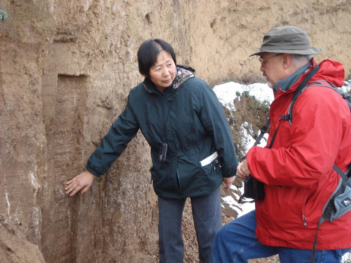 Weijian Zhou  of the Chinese Academy of Sciences in Xi'an and Warren Beck  of the University of Arizona at a cross-section of a hill near Xi'an, China, examining layers of loess soil that represent thousands of years of soil deposition.