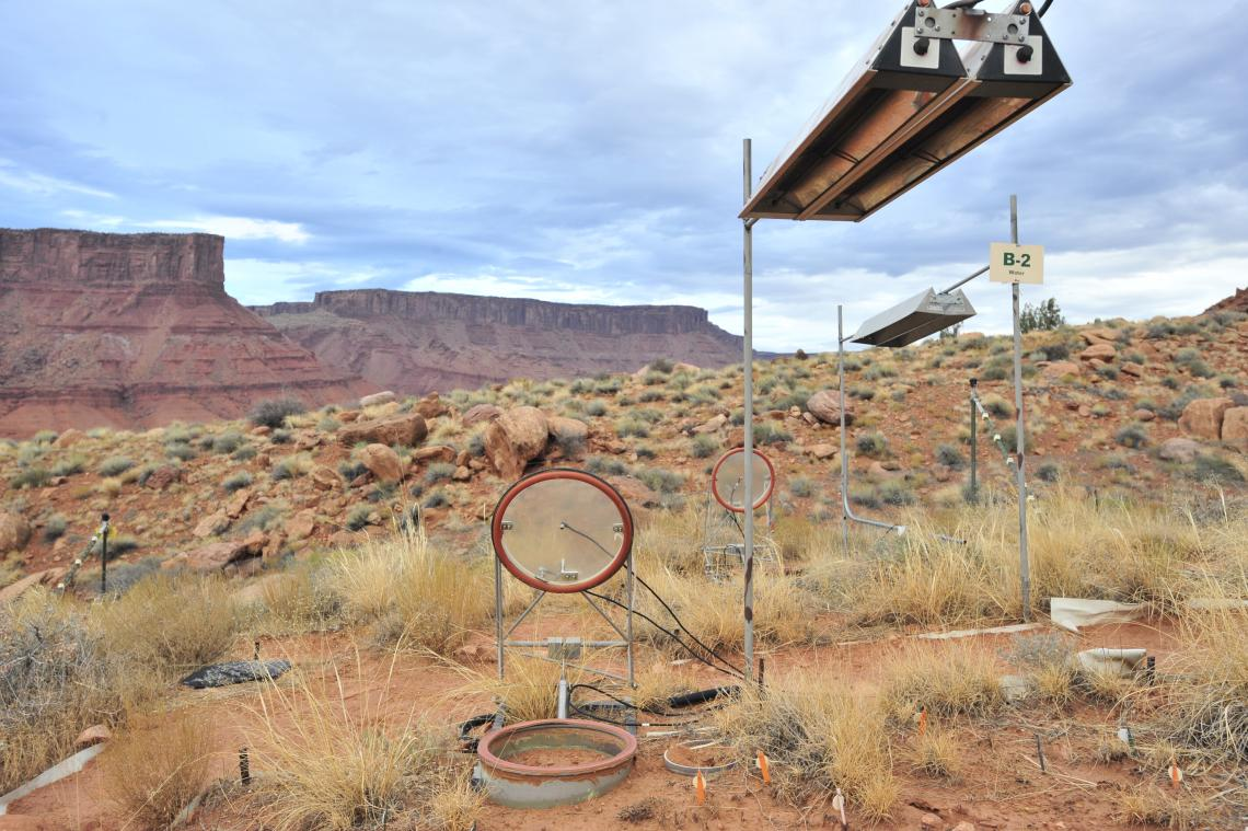 A climate manipulation study site near Moab, Utah, where the albedo measurements were made. The study areas are warmed using infrared lamps hanging above. Also pictured is a carbon dioxide soil respiration chamber placed in the study area to understand th