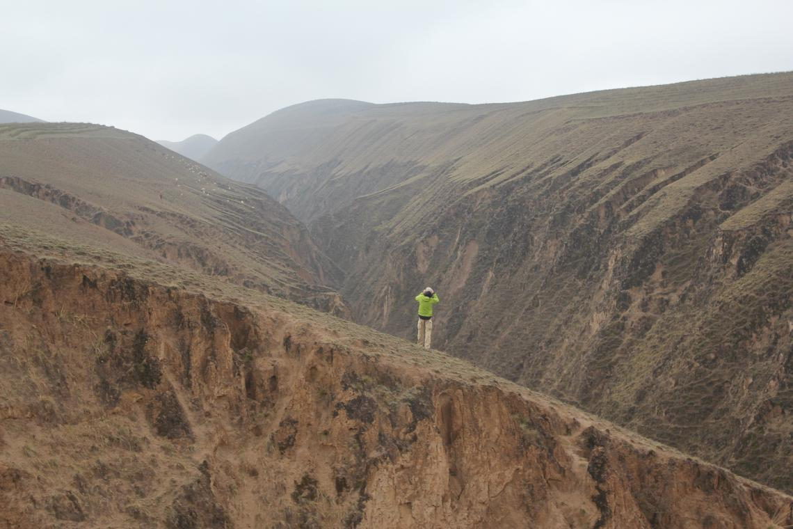 Geoscientist Fulong Cai stands on a linear ridge on top of China's Loess Plateau and looks across a river valley at another of the plateau's linear ridges. The high hills in the far background are on the edge of the plateau, which drops about 1,300 feet t