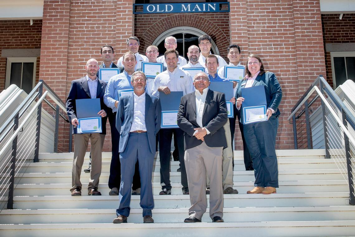 John Kemeny , chair of the UA Department of Mining and Geological Engineering, and Victor Tenorio , MGE professor of practice, with the inaugural class of 12 graduates of the Mining 360 Program.