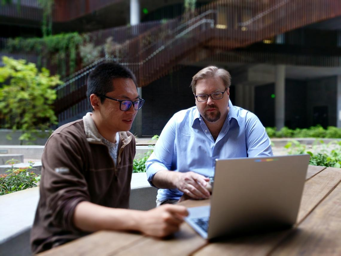 Assistant professor Mike Barker  and graduate student Zheng Li review data from their bioinformatic search.