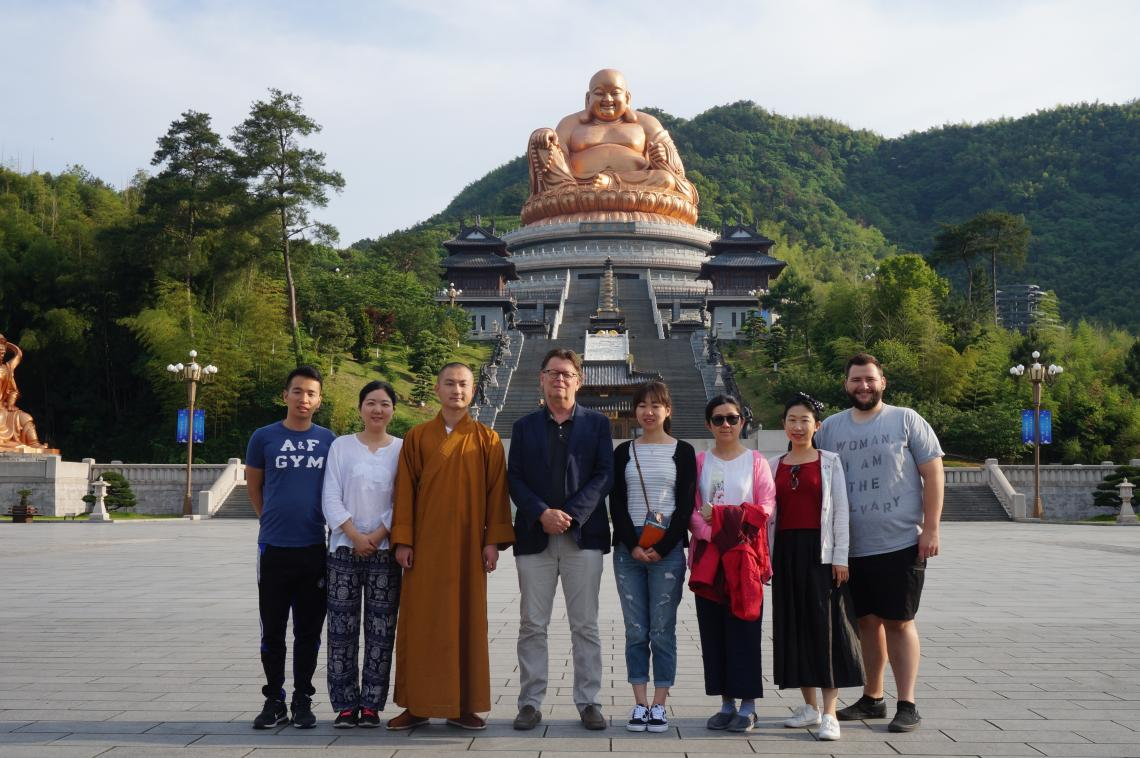 In front of the statue of Maitreya Buddha at Xuedou  Monastery with the abbot, UA professor Albert Welter and UA graduate students