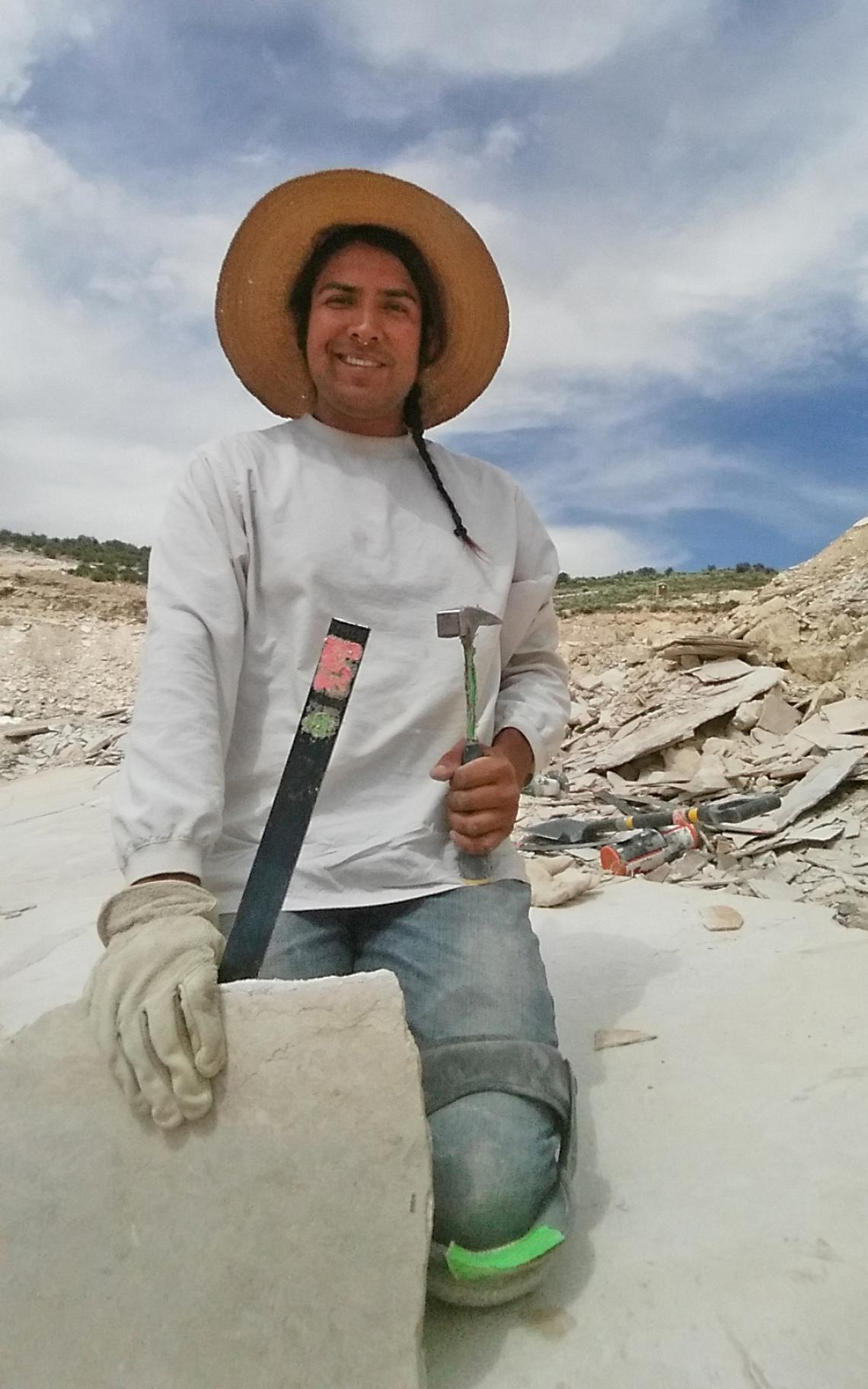 In the GeoDecor quarry near Kemmerer, Wyoming, GeoPathways student Jesse Clah hunts for fossil fish in a slab of Green River formation limestone.