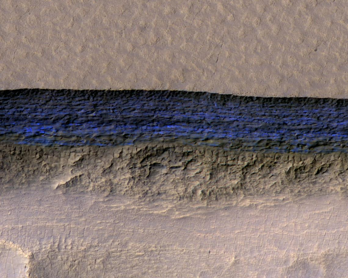 At this pit on Mars, the steep slope at the northern edge  exposes a cross section of a thick sheet of underground water ice. The image is from the HiRISE camera on NASA's Mars Reconnaissance Orbiter, with an enhanced-color central swath between grayscale