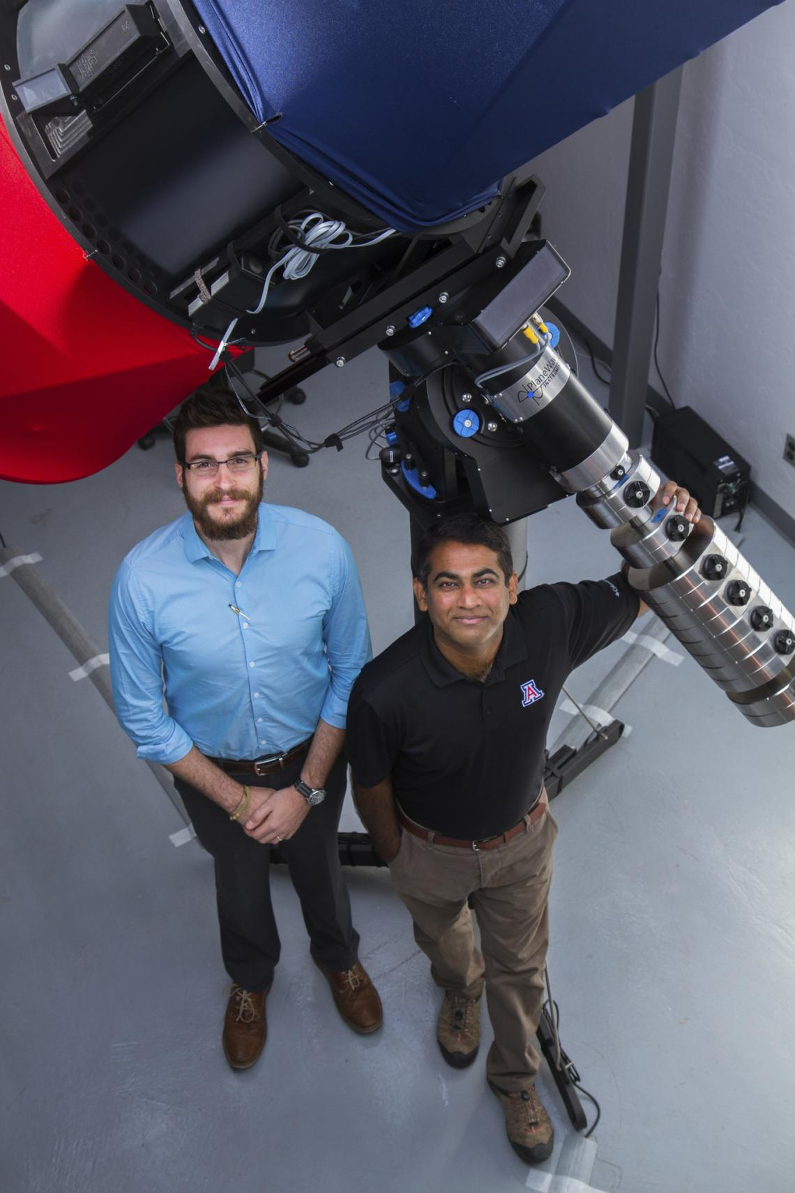 Vishnu Reddy  and Tanner Campbell stand next to the RAPTORS telescope at the UA's Kuiper Space Sciences building. They would like to mount an optical sensor system on the telescope in the future.