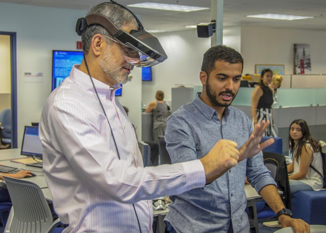 International student Hazza Alkaabi  helps UA honorary degree recipient Mohammed Sharaf experience augmented reality.