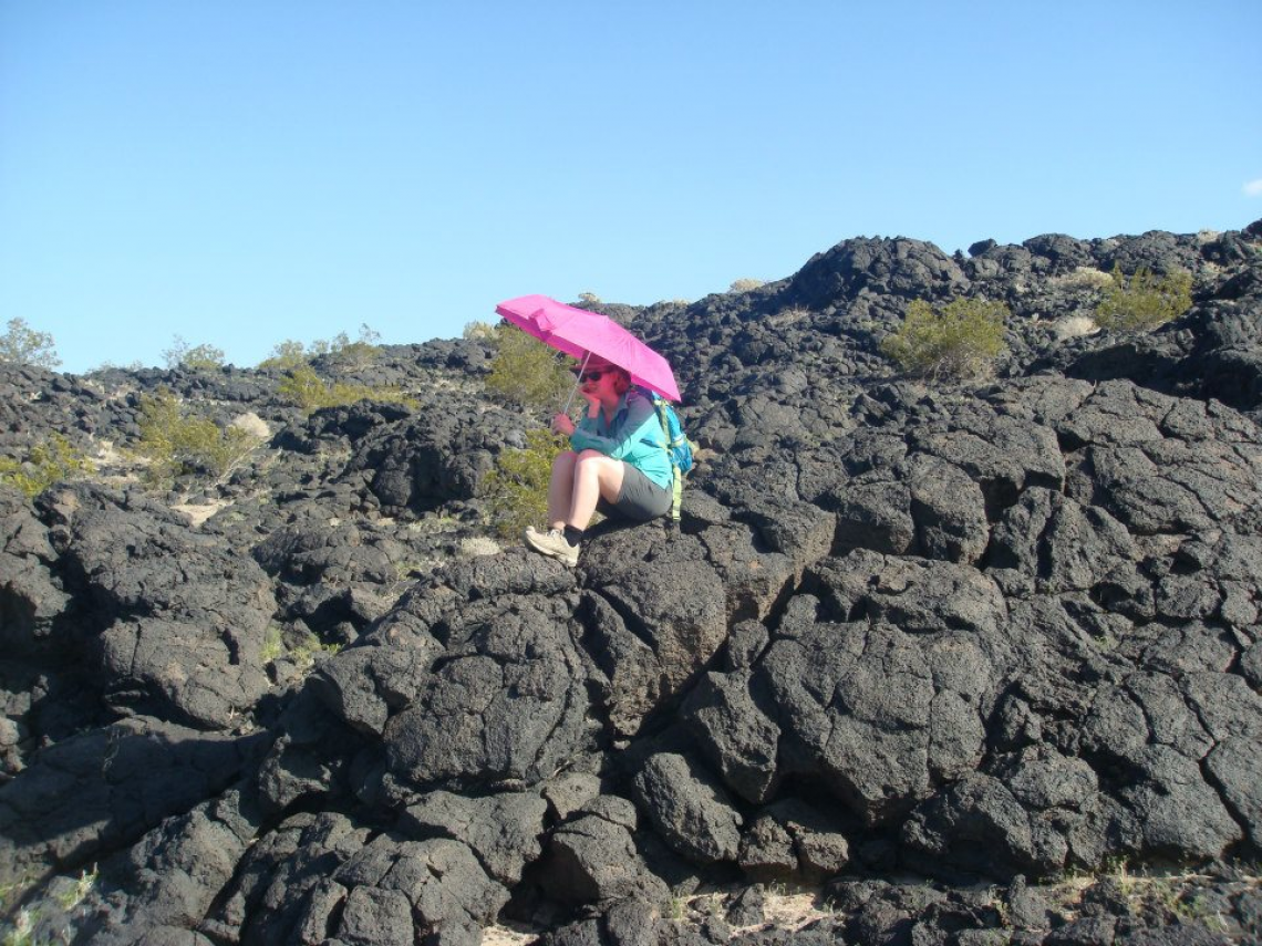 A University of Arizona Lunar and Planetary Laboratory student holds a bright umbrella over the spot where she found geologic contact between two different lava flows during a trip to Amboy Crater in California's Mojave Desert.