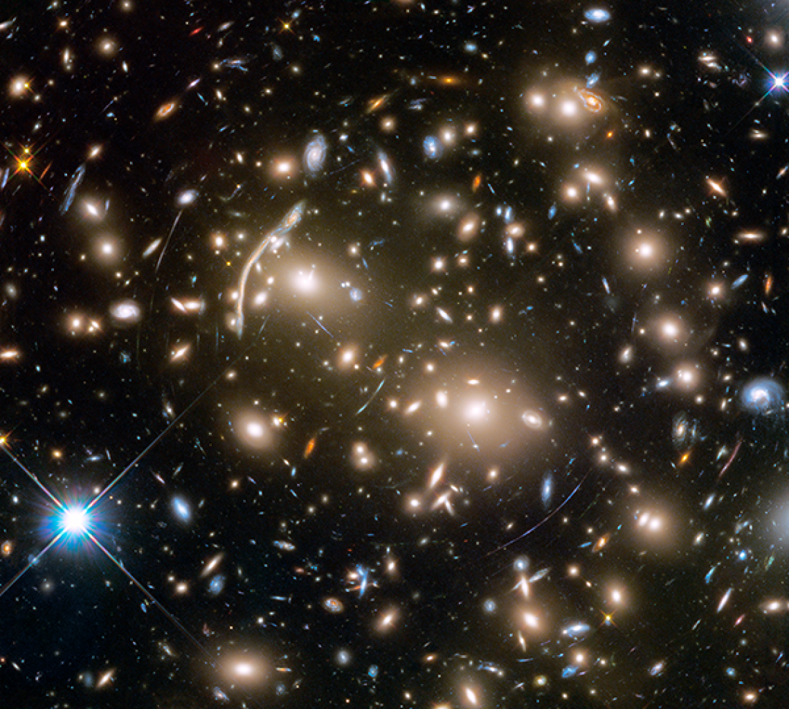The Hubble Space Telescope took this image of Abell 370, a galaxy cluster 4 billion light-years from Earth. Several hundred galaxies are tied together by gravity. The arcs of blue light are distorted images of galaxies far behind the cluster, too faint fo
