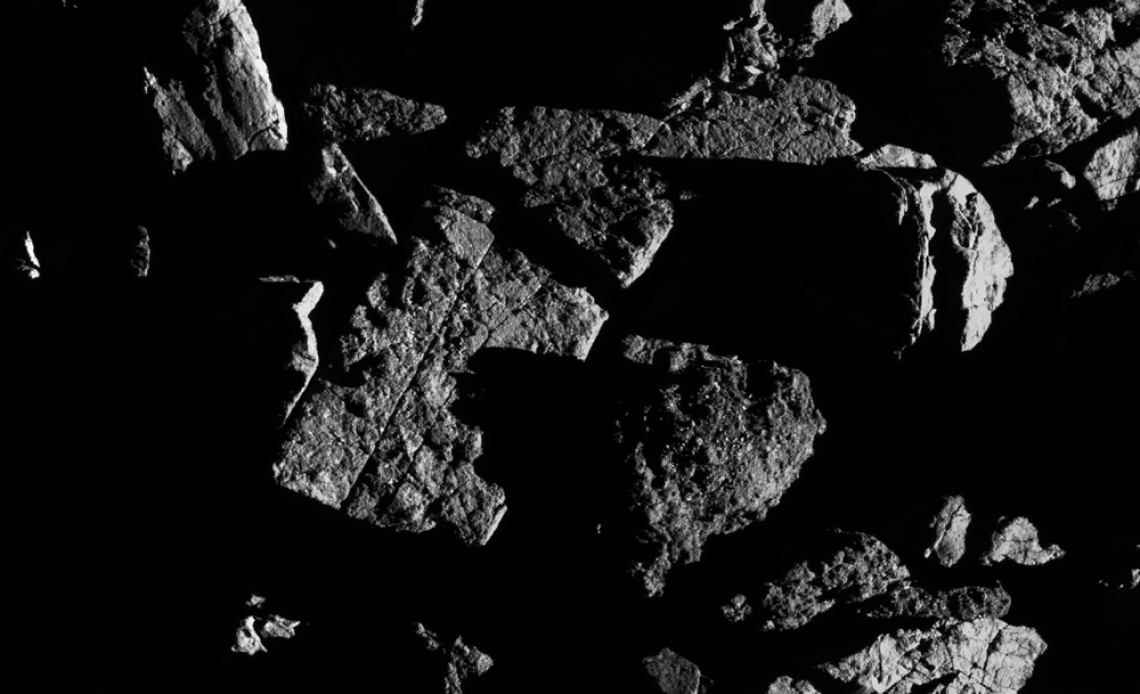 This image, taken by the spacecraft from a distance of 0.4 miles, shows a group of large boulders located just north of asteroid Bennu's equatorial region, with two exhibiting linear cracks. For scale, the crack that runs through the rectangular boulder