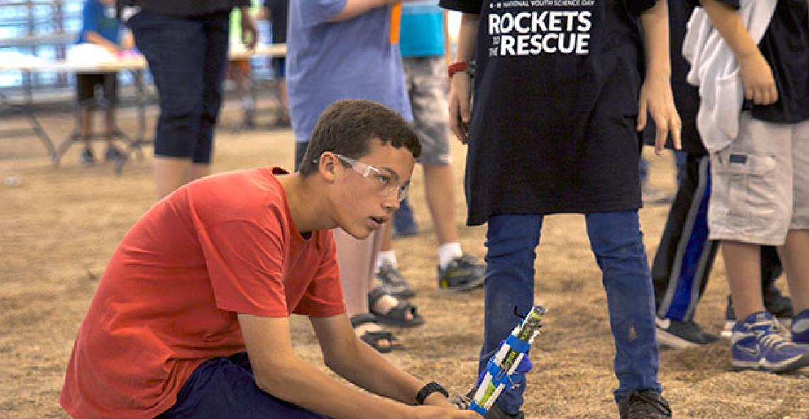 A 4-H National Youth Science Day participant prepares a rocket for launch.