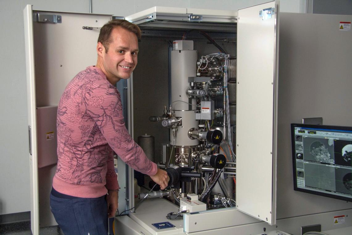 Pierre Haenecour, the study's lead author, is pictured with one of the ultra-high-resolution electron microscopes used to obtain chemical and microstructural information about the stardust grain.