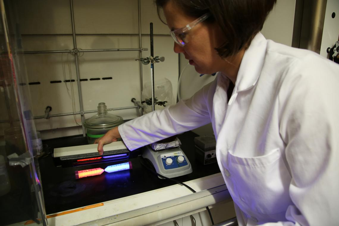 Co-inventor Colleen Janczak uses a fluorescent light to illuminate the new nanomaterials.
