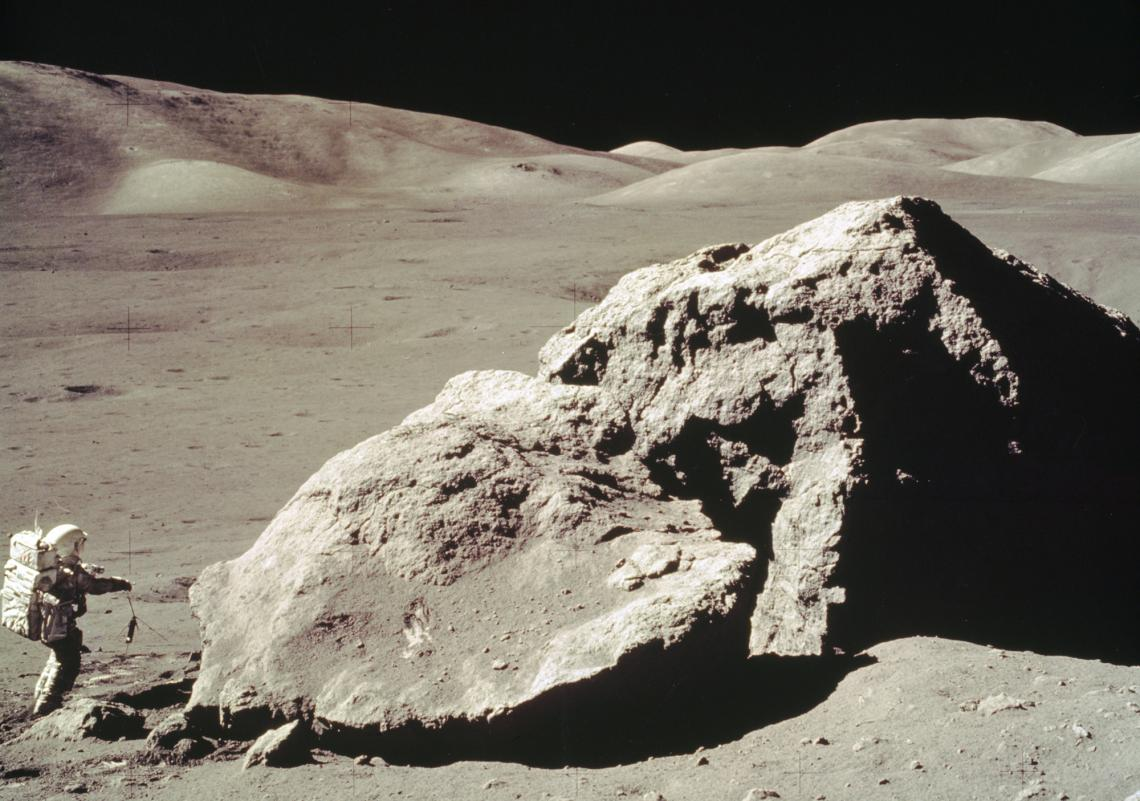In this Apollo 17 onboard photo, scientist and astronaut Harrison H. Schmitt collects rock samples from a huge boulder near the Valley of Tourus-Littrow on the lunar surface.
