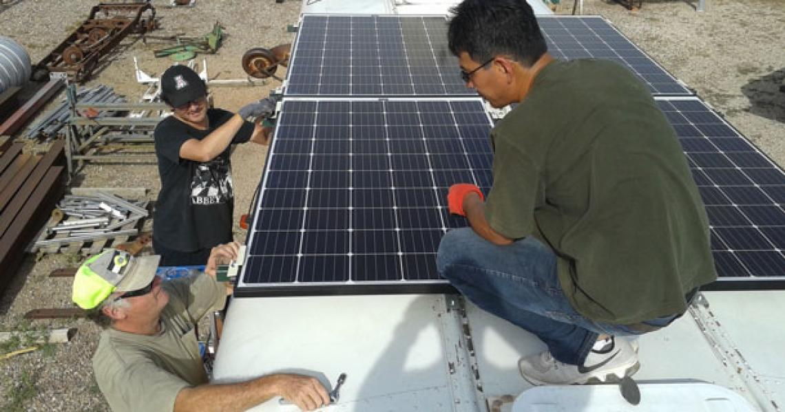 Members of the UA-AATech team mount the solar panels on the roof of the school bus. From left: Bob Seaman, technical lead for desalination unit assembly; environmental engineering master's student Chris Yazzie; and AATech president Peter Zhou. Yazzie was